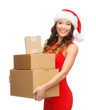 package delivery: christmas, x-mas, winter, happiness concept - smiling woman in santa helper hat with many parcel boxes Stock Photo