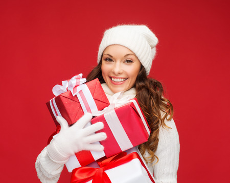nice girl: christmas, x-mas, winter, happiness concept - smiling woman in sweater and hat with many gift boxes