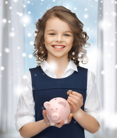 banking, finances, investment and happy people concept - beautiful girl with piggy bank photo
