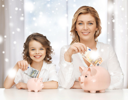 banking, finances, investment and happy people concept - mother and daughter with piggy banks and paper money photo
