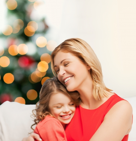 christmas, x-mas, winter, happiness concept - hugging mother and daughter photo