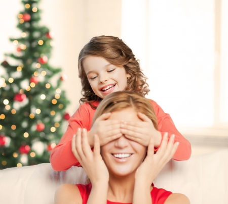 christmas, x-mas, winter, happiness concept - mother and daughter making a joke photo