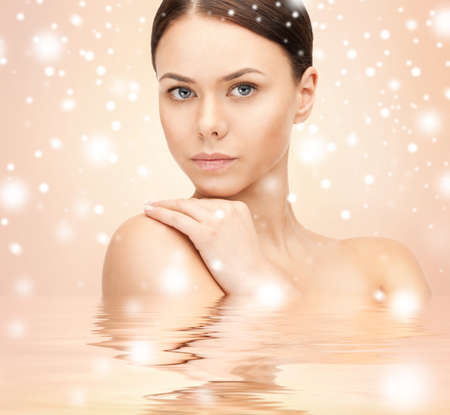 health, spa, beauty concept - face, hands and shoulders of beautiful woman photo