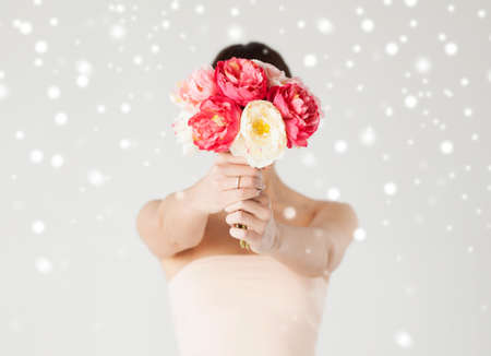 valentines day, bridal, wedding, christmas, x-mas, winter, happiness concept - young woman holding bouquet of flowers over her face photo