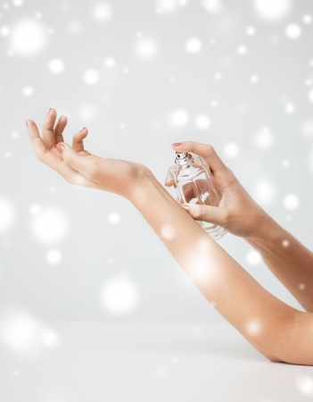 health and beauty concept - woman hands spraying perfume photo