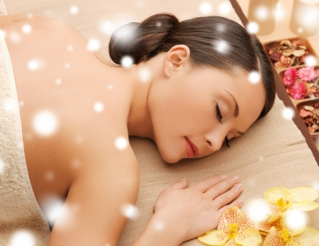 health and beauty concept - woman in spa salon lying on the massage desk photo