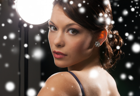 luxury, vip, nightlife, party, christmas, x-mas, new year's eve concept - beautiful woman in evening dress wearing diamond earrings photo