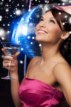cocktail party: luxury, vip, nightlife, party, christmas, x-mas, new years eve concept - beautiful woman in evening dress with cocktail and disco ball Stock Photo