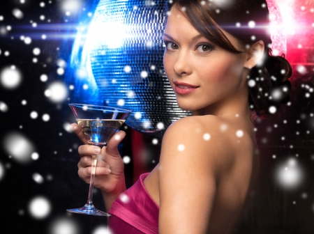 vip: luxury, vip, nightlife, party, christmas, x-mas, new years eve concept - beautiful woman in evening dress with cocktail and disco ball Stock Photo