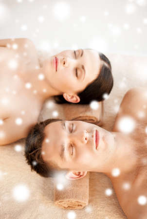 health and beauty concept - couple in spa salon lying on the massage desks photo
