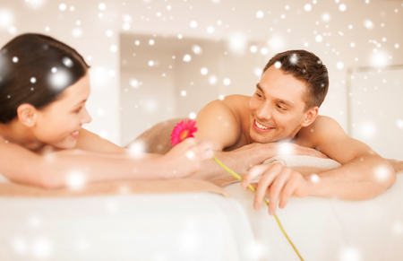 health and beauty, love, romance concept - couple in spa salon lying on the massage desks photo