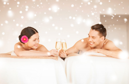 health and beauty, love, romance concept - couple in spa salon drinking champagne photo