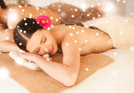 health and beauty concept - couple in spa salon with hot stones photo