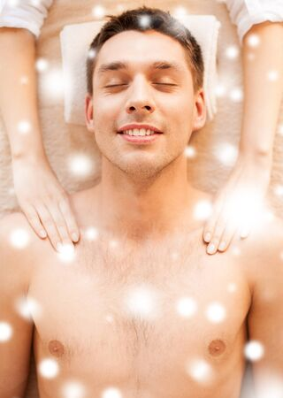 health and beauty concept - man in spa salon getting massage photo