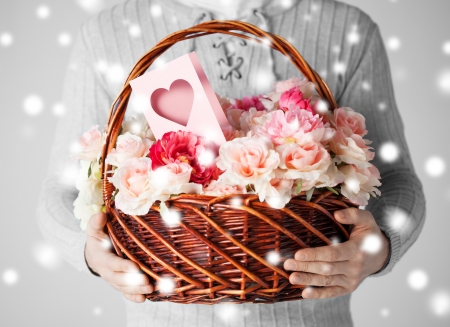 valentines day, christmas, x-mas, winter, happiness concept - man holding basket full of flowers and postcard photo