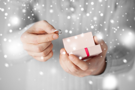 valentines day, christmas, x-mas, winter, happiness concept - man holding wedding ring and gift box photo