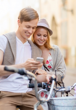 summer holidays, bikes, love, relationship, navigation, gps and dating concept - couple with bicycles and smartphone in the city photo