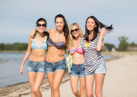 summer, holidays, vacation, happy people concept - group of girls in bikinis walking on the beach photo