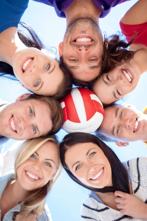 mates: summer, holidays, vacation, happy people concept - group of teenagers with ball looking down