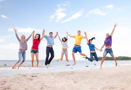 été, vacances, vacances, les gens heureux de concept - groupe d'amis sautant sur la plage