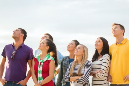 summer, holidays, vacation, happy people concept - group of friends looking up on the beach photo