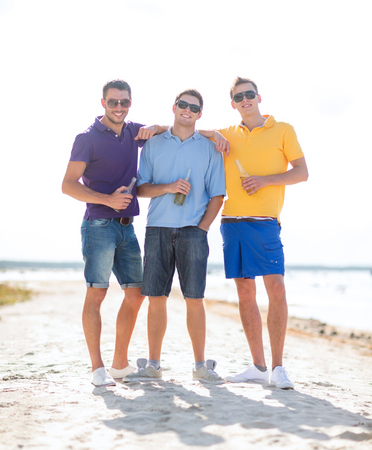 nonalcoholic beer: summer, holidays, vacation, happy people concept - group of friends having fun on the beach with bottles of beer or non-alcoholic drinks Stock Photo