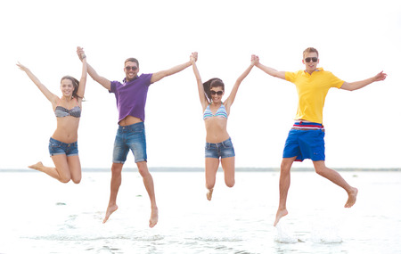 happy people jumping: summer, holidays, vacation, happy people concept - group of friends or couples jumping on the beach