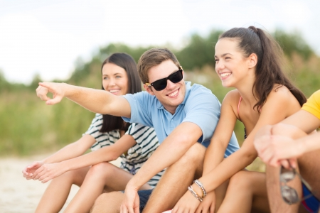 summer, holidays, vacation, happy people concept - group of friends pointing somewhere on the beach