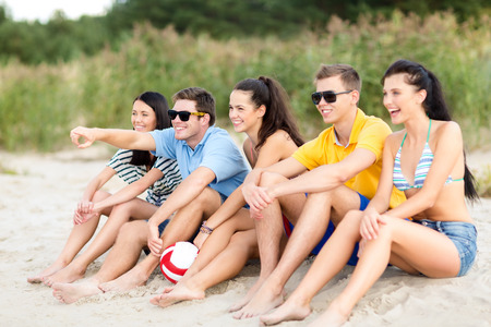 chilling out: summer, holidays, vacation, happy people concept - group of friends or volleyball team having fun on the beach