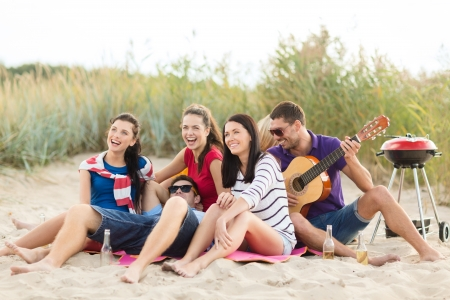 boy playing guitar: summer, holidays, vacation, music, happy people concept - group of friends with guitar having fun on the beach