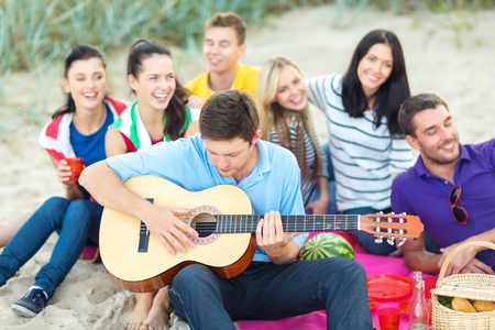 playing in the sea: summer, holidays, vacation, music, happy people concept - group of friends with guitar having fun on the beach