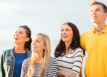 good looking boy: summer, holidays, vacation, happy people concept - group of friends looking up on the beach