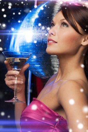 luxury, vip, nightlife, party, christmas, x-mas, new year's eve concept - beautiful woman in evening dress with cocktail and disco ball photo