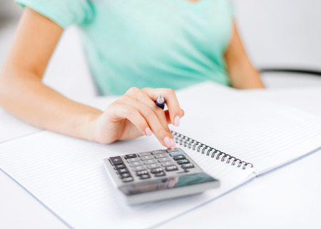 finance girl: business concept - businesswoman working with calculator in office