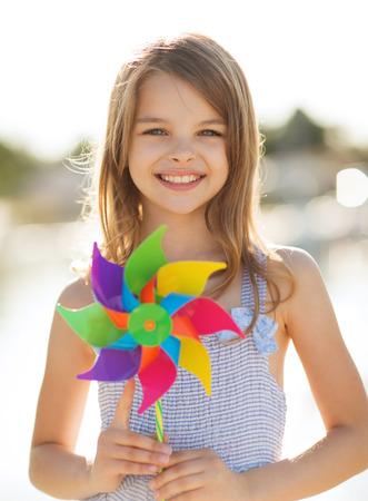 夏の休日、祭典、家族、子供、人のコンセプト - カラフルな風車のおもちゃで幸せな女の子
