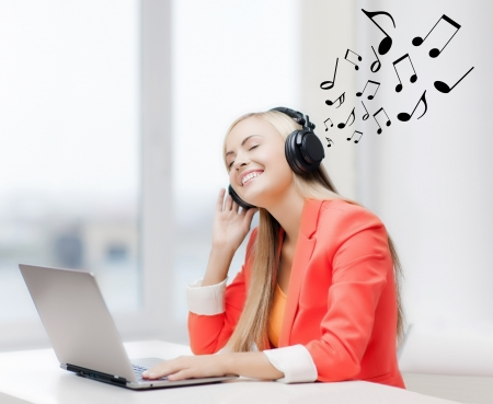 leisure, music, free time, online and internet concept - happy woman with headphones listening to music photo