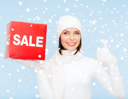 shopping, gifts, christmas, x-mas concept - smiling woman in winter clothes with red sale sign and thumbs up photo