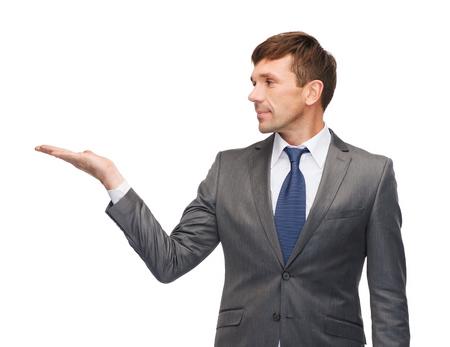 zakelijke en office concept - aantrekkelijke buisnessman of leraar die iets op de palm