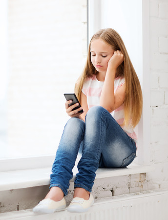education, school, technology and internet concept - little student girl with smartphone at school