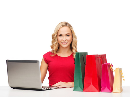 christmas, x-mas, online shopping concept - woman with shopping bags and laptop computer photo