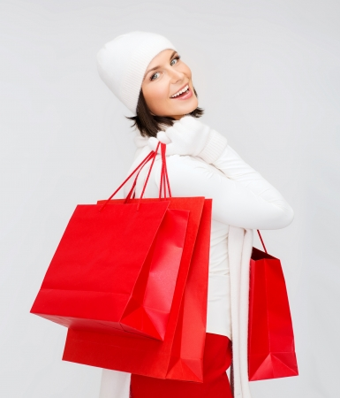 overspending: retail and sale concept - happy woman in winter clothes with shopping bags Stock Photo