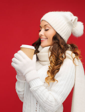 winter, people, happiness, drink and fast food concept - woman in hat with takeaway tea or coffee cup photo