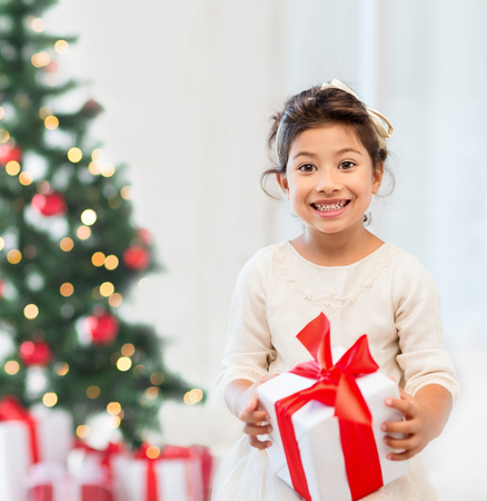 christmas girl: holidays, presents, christmas, x-mas concept - happy child girl with gift box