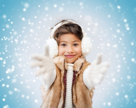 winter, people, happiness concept - happy little girl in winter clothes photo