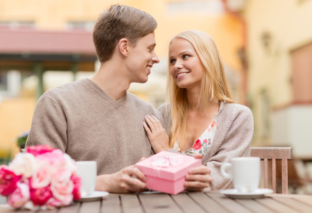 summer holidays, love, travel, tourism, relationship and dating concept - romantic happy couple with gift in the cafe