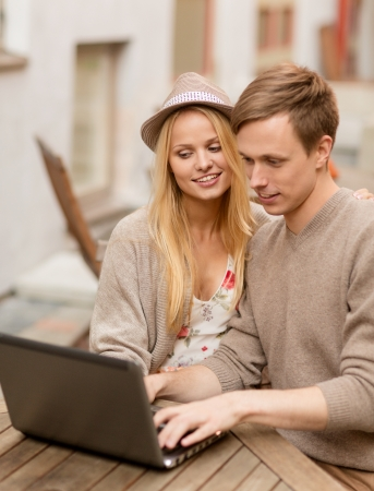 summer holidays, city, dating and technology concept - couple with laptop in cafe photo
