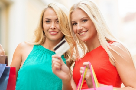 gift spending: sale and tourism, happy people concept - beautiful women with shopping bags and credit card in the ctiy Stock Photo