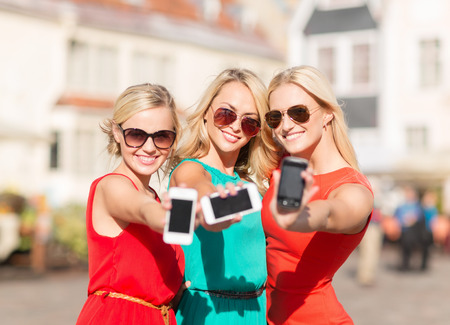 street party: holidays and tourism, modern technology concept - beautiful blonde girls with smartphones in the city Stock Photo