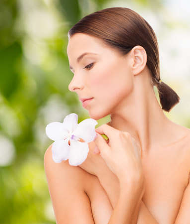 health and beauty, eco, bio, nature concept - relaxed woman with orchid flower photo