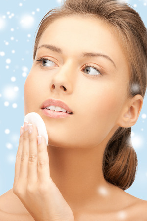 health and beauty concept - beautiful woman with cotton pad photo